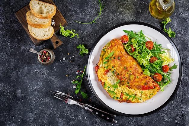 朝ごはん。トマト、アボカド、ブルーチーズ、グリーンピースと白い皿のオムレツ。フリッタータ-イタリアのオムレツ。上面図 Premium写真