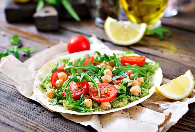 Веганские тако с гуакамоле, нутом, помидорами и рукколой. здоровая пища. полезный завтрак Бесплатные Фотографии