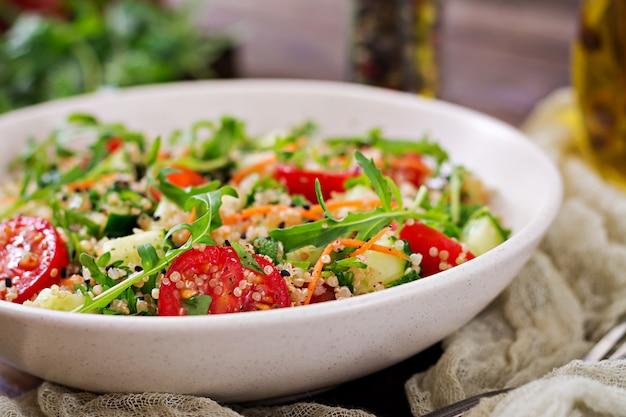 キノア、ルッコラ、大根、トマト、キュウリのボウルに木製のテーブルのサラダ。健康食品、ダイエット、デトックス、ベジタリアンのコンセプト。 無料写真