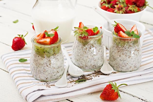 瓶の中のデトックスと健康的なスーパーフードの朝食。ビーガンココナッツミルクチアシードプリンとイチゴとキウイ。 Premium写真
