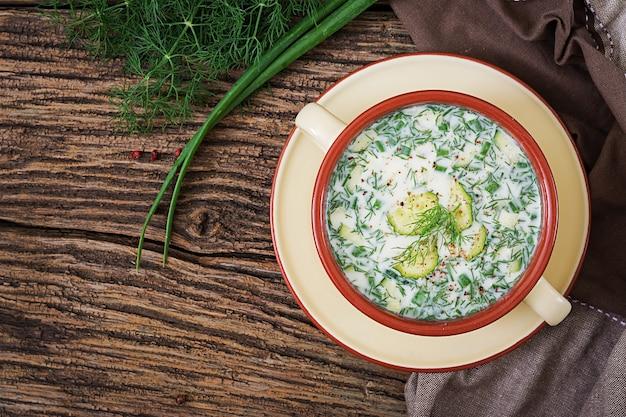 卵、キュウリ、木製のテーブルのディルと夏のヨーグルトの冷たいスープ。オクローシカ。ロシア料理。上面図。平干し。 Premium写真