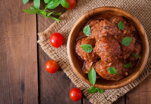 Фрикадельки в кисло-сладком томатном соусе с базиликом в деревянной миске Бесплатные Фотографии
