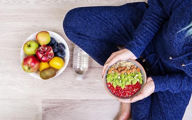 Фитнес и концепция здорового образа жизни. женщина отдыхает и ест здоровую овсянку после тренировки. вид сверху. Бесплатные Фотографии