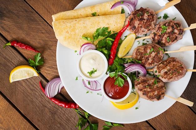 白いプレートにソースとトルティーヤタコスと食欲をそそるコフタケバブ(ミートボール) 無料写真