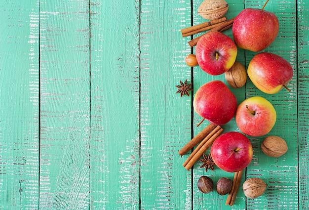 明るい木製の背景にバスケットで熟した赤いリンゴ。 Premium写真