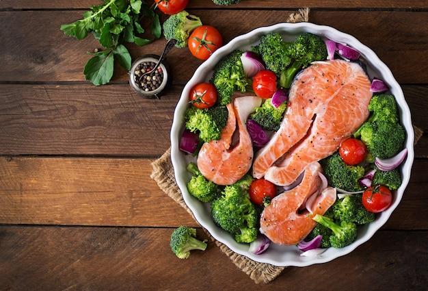生サーモンステーキと素朴なスタイルの暗い木製の背景で調理するための野菜。上面図 Premium写真