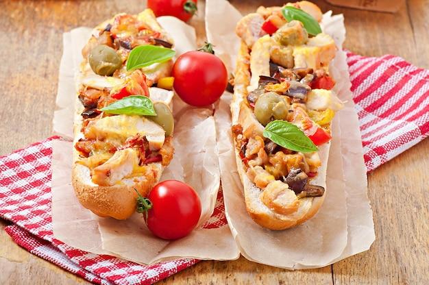ロースト野菜と鶏肉のチーズとバジルの古い木製の表面の大きなサンドイッチ 無料写真