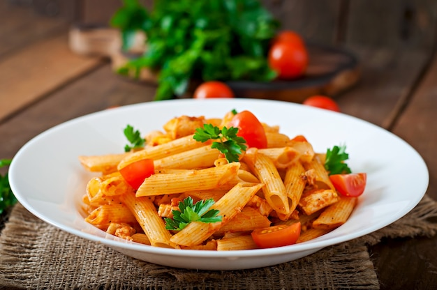 鶏肉とトマトの木製テーブルのトマトソースのペンネパスタ Premium写真