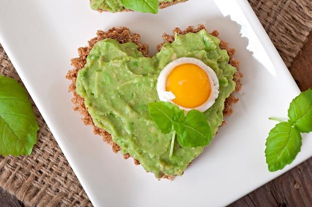 アボカドペーストとハートの形の卵のサンドイッチ 無料写真