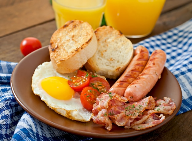 イングリッシュブレックファースト-木製の表面に素朴なスタイルのトースト、卵、ベーコン、野菜 Premium写真
