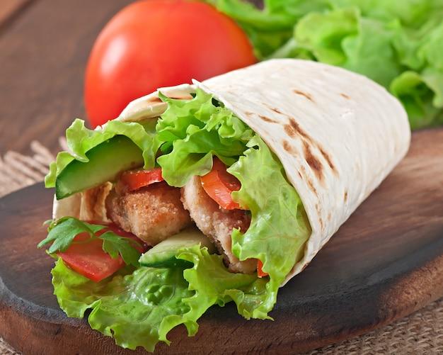 新鮮なトルティーヤをチキンナゲットと野菜のプレートで包みます Premium写真