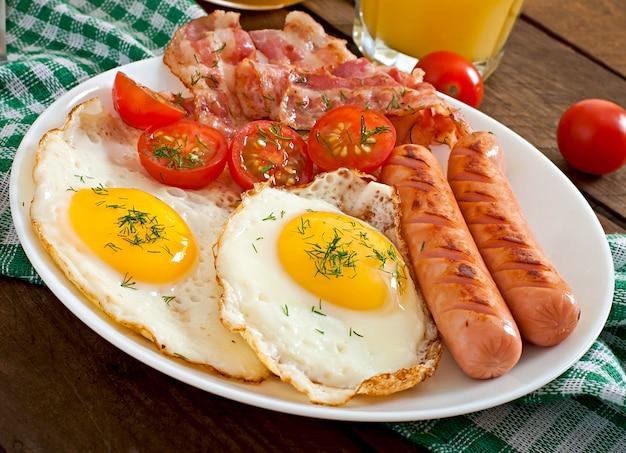 木製のテーブルで素朴なスタイルのトースト、卵、ベーコン、野菜のイングリッシュブレックファースト Premium写真