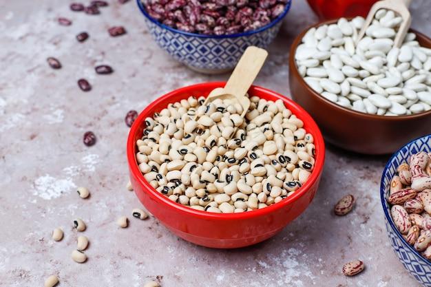 Бобовые и фасоль ассортимент в разные чаши на светлом фоне каменных. вид сверху. здоровая веганская протеиновая пища. Premium Фотографии