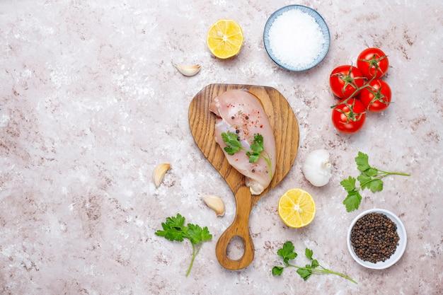 Сырые филе куриной грудки на деревянной разделочной доске с травами и специями. вид сверху Premium Фотографии