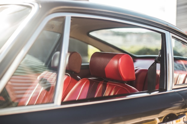 Винтажный автомобиль в автосалоне, красный салон и сиденья Premium Фотографии