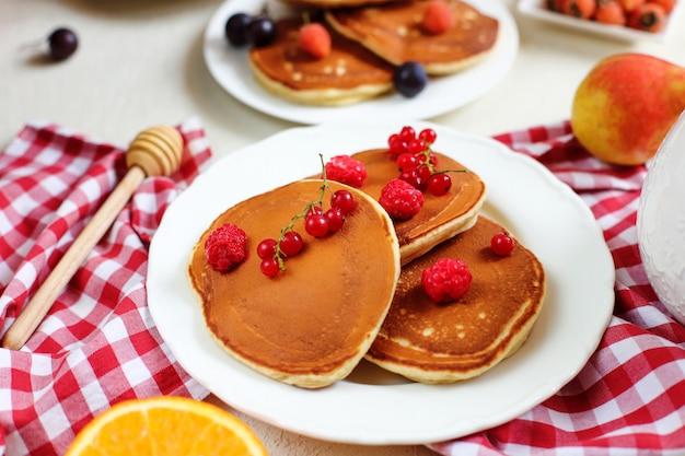 健康的な夏の朝食、新鮮なベリーと蜂蜜と自家製の古典的なアメリカのパンケーキ Premium写真