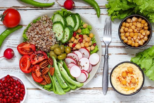 フムスのボウル、野菜スティック、ヒヨコ豆、オリーブ。 Premium写真