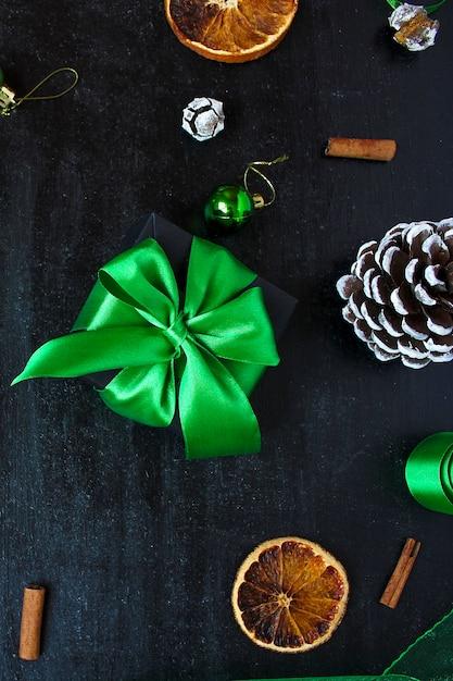 乾燥したオレンジ、白い松ぼっくり、緑のクリスマスツリーのボール、みかん、赤いリンゴ、ジンジャースティックとクリスマスの背景、 Premium写真