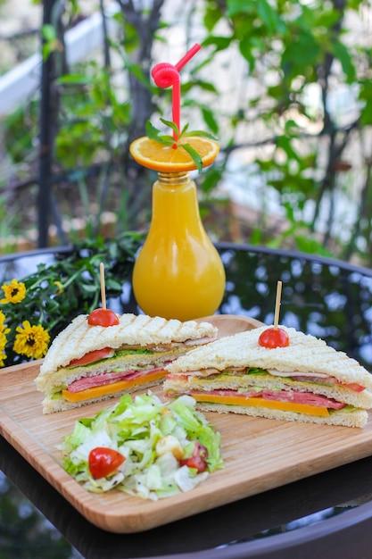 黒いガラステーブルにオレンジジュースのクラブサンドイッチ 無料写真