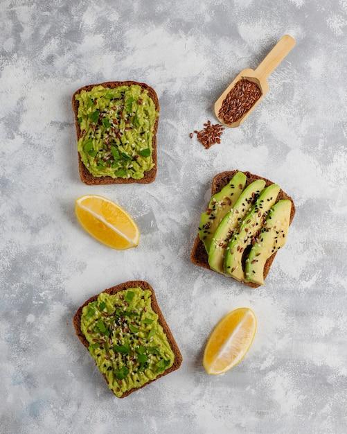 Авокадо открытый тост с ломтиками авокадо, лимоном, семенами льна, кунжутом, ломтиками черного хлеба, вид сверху Бесплатные Фотографии