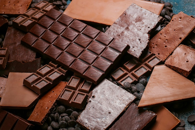 Куски темного, белого и молочного шоколада. вид сверху Premium Фотографии