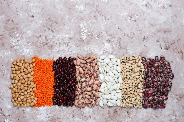 Бобовые и фасоль ассортимент в разные чаши на светлом фоне каменных. вид сверху. здоровая веганская протеиновая пища. Бесплатные Фотографии