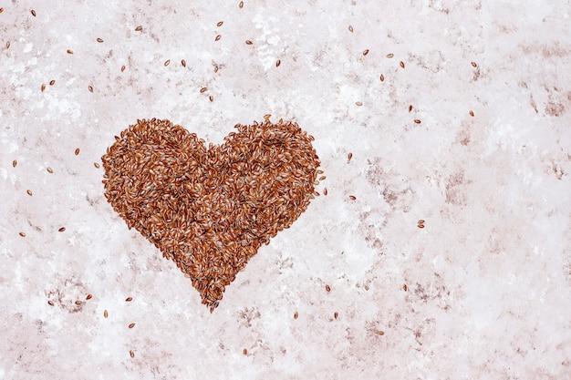 Семена льна в форме сердца на конкретном фоне с пространством для копирования, вид сверху Бесплатные Фотографии