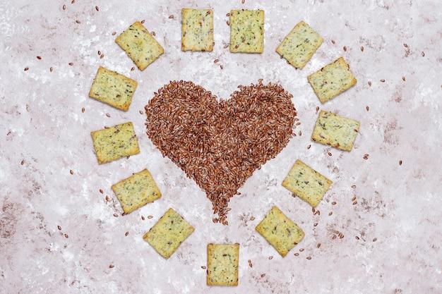 Крекеры в форме сердца из льняных семян с оливковым маслом, льняными семенами и зеленью, вид сверху Бесплатные Фотографии