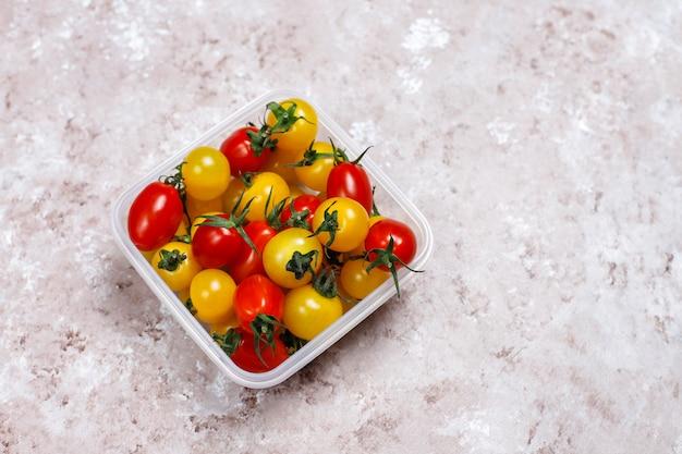 明るい背景にさまざまな色、黄色と赤のチェリートマトのチェリートマト 無料写真