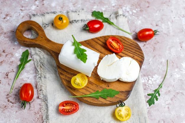 Кусочки козьего сыра на деревянной доске с рукколой, помидорами черри. готовы есть. Бесплатные Фотографии