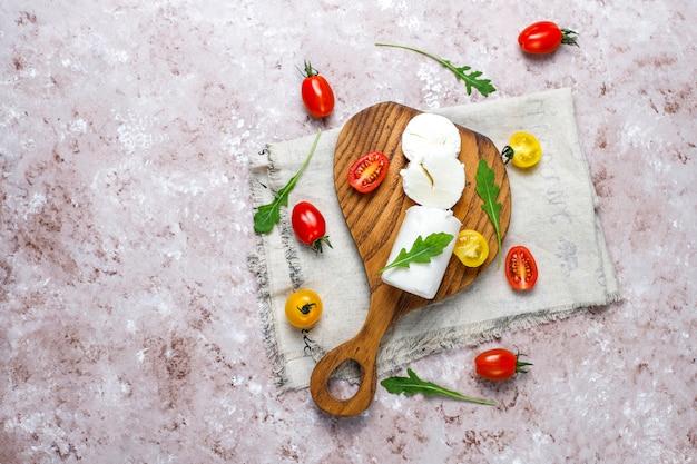ルッコラ、チェリートマトと木の板にヤギのチーズスライス。食べる準備ができました。 無料写真