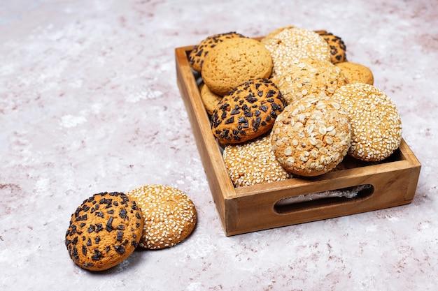 Комплект различных печений американского стиля в деревянном подносе на светлой конкретной предпосылке. песочное печенье с кунжутом, арахисовым маслом, овсянкой и шоколадным печеньем. Бесплатные Фотографии