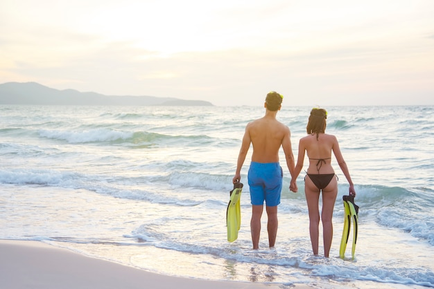 カップルは夕暮れ時のビーチの上に立っています。 Premium写真
