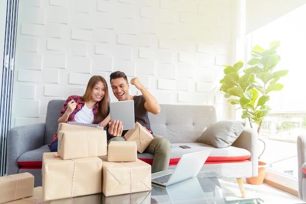 Пара счастлива после успешной онлайн продажи дома. малый бизнес с технологией концепции. Premium Фотографии