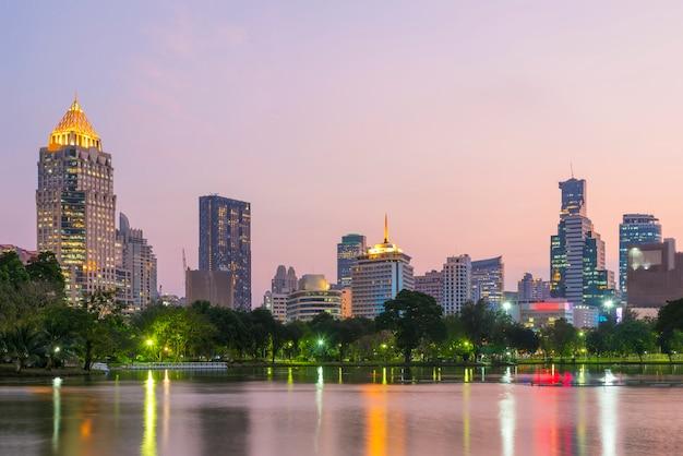 夕暮れ時のバックグラウンドでバンコクのビジネスセンター地区の高い建物とルンピニー公園の湖。 Premium写真