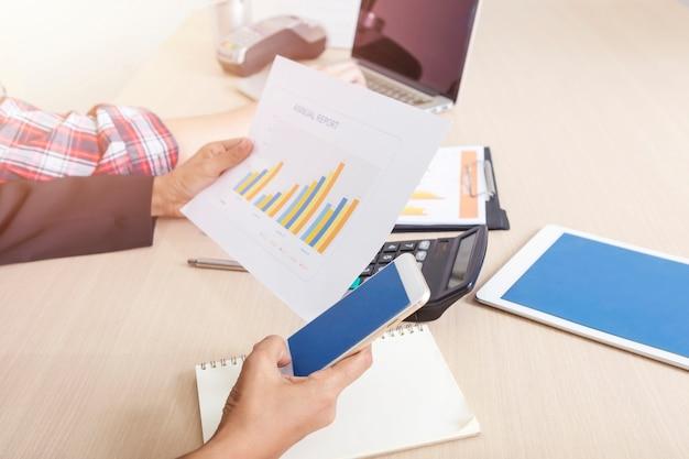 ビジネスと金融の概念携帯と事務処理のレポートが付いているオフィスで働く人々をクローズアップ。 Premium写真