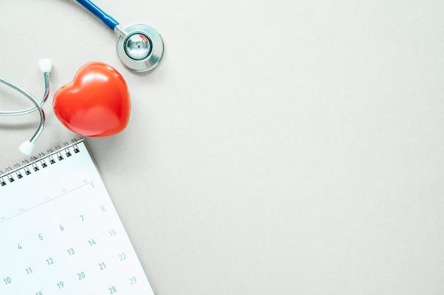 赤いハート、聴診器、空き容量の白いテーブルの上のカレンダー。 Premium写真