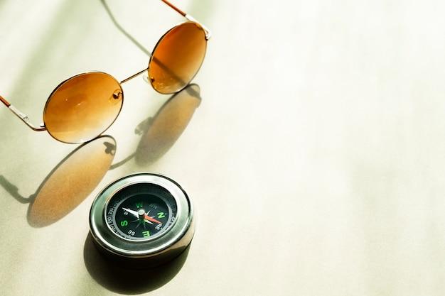 背景の概念を旅行します。コンパスと反射の影付きのテーブルの上のサングラス。 Premium写真