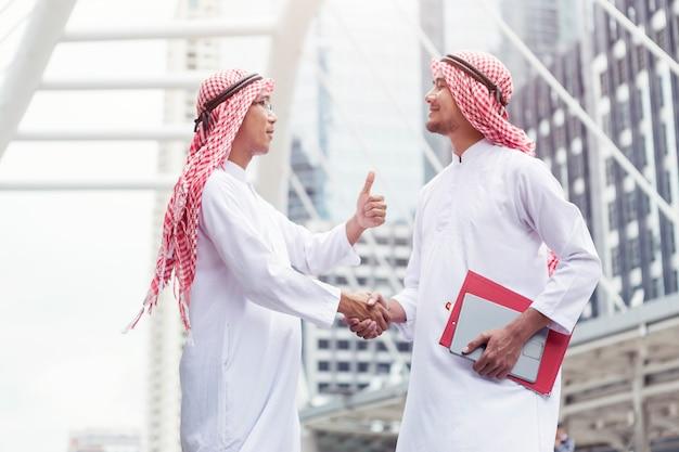 商取引の成功、アラブは都市で握手を交わしています。 Premium写真
