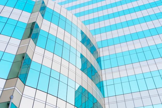 空と雲の反射とモダンな建物の青い眼鏡窓から抽象的な背景。 Premium写真