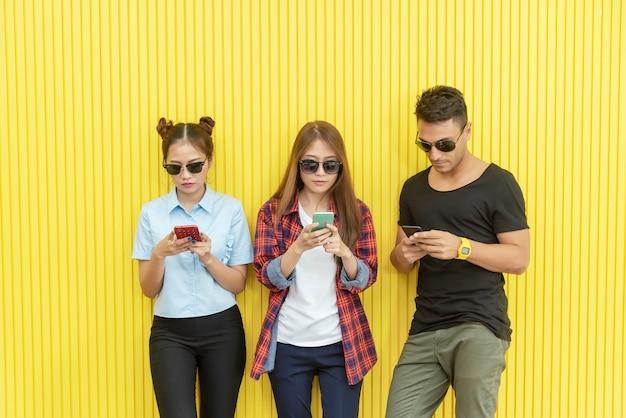 壁にスマートフォンを使用している若い人々のグループ。ネットワーク接続技術 Premium写真