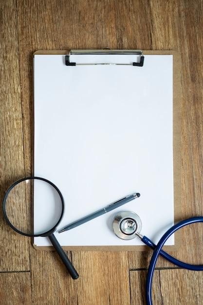 テーブルの上の空白のノートブックに聴診器で拡大鏡。医学的背景のコンセプトです。 Premium写真