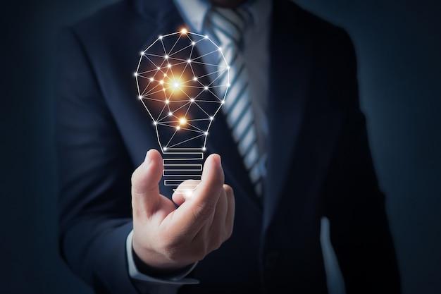 Деловой человек, держащий в руке яркую лампочку Premium Фотографии