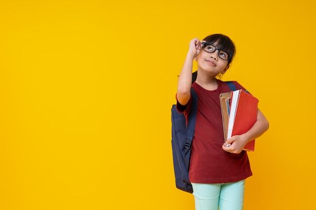 メガネで本を保持していると黄色で見上げるアジアの子供学生の肖像画 Premium写真