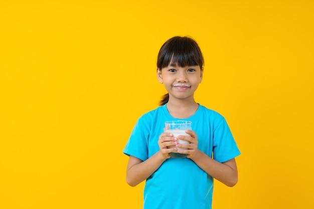 Счастливый тайский ребенок, держа стакан молока, изолированные, молодая азиатская девушка, пить молоко Premium Фотографии