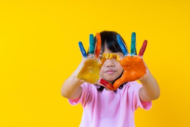 Портрет молодой азиатской девушки с искусством, тайский забавный малыш показывает акварель на ладони в форме сердца, творчество детей и концепцию живописи любви Premium Фотографии