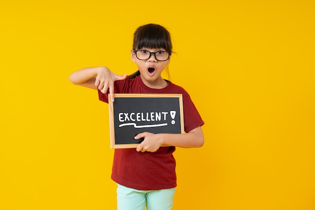 優秀な言葉で小さな黒板を指して、すごい、仕事で驚いた女子学生 Premium写真