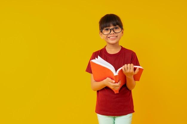 眼鏡と赤いシャツを着て笑顔で若いアジア女子学生を開き、本を読む Premium写真