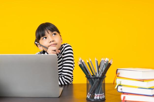 Азиатский ребенок сидит и думает с ноутбуком и столом Premium Фотографии