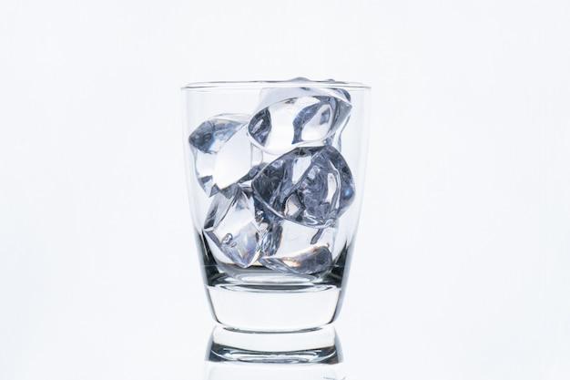 白い壁に分離されたアイスキューブとガラス Premium写真